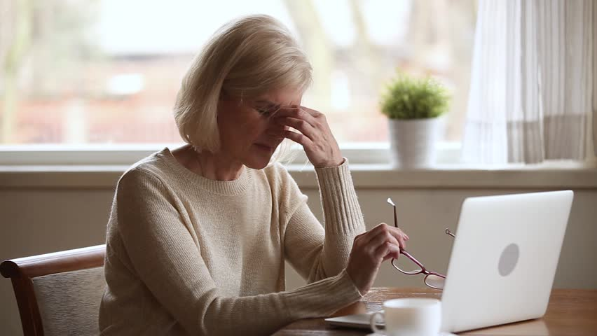 Senior woman using laptop feeling discomfort from dry irritated fatigued eyes taking off glasses, older mature businesswoman tired of computer worker suffering from blurry vision eyestrain problem | Shutterstock HD Video #1024093982