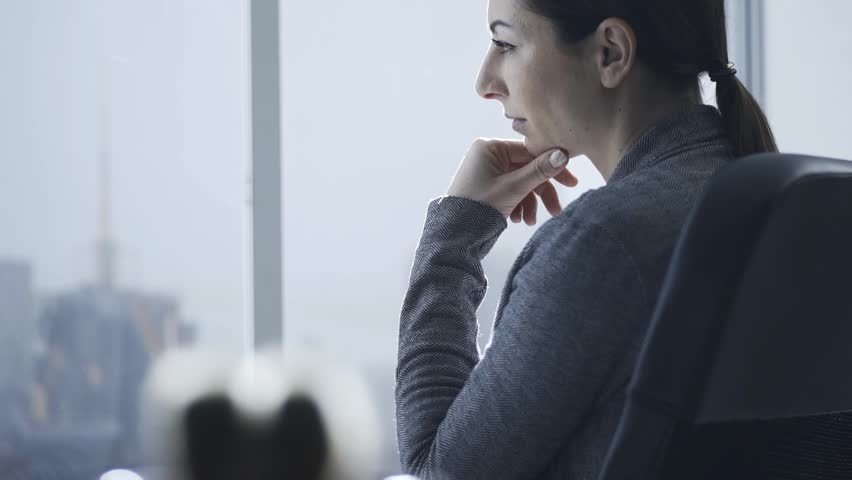 Pensive confident businesswoman staring at the office window, she is looking at the city skyline and thinking | Shutterstock HD Video #1024109582