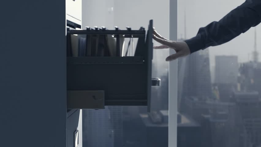 Office worker closing a filing cabinet's drawer and city view in the background