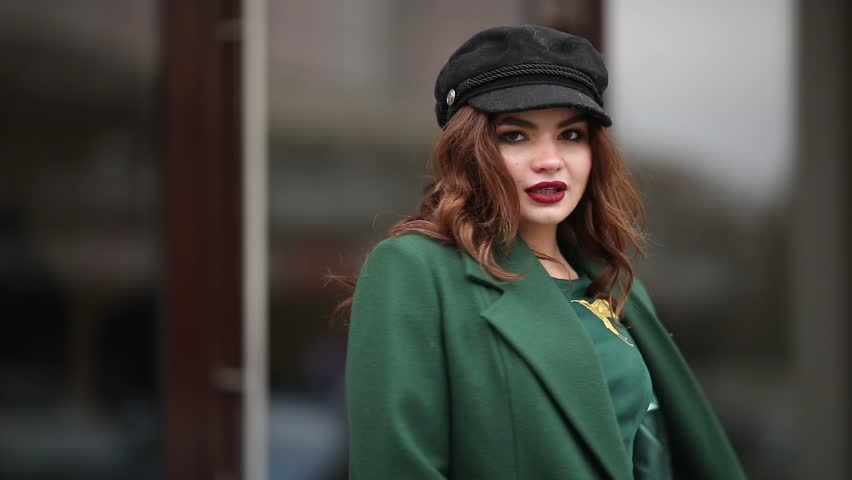 Portrait of charming smiling brunette with red lips wearing trendy black cap and green coat with dragonfly brooch. She is twisting and smiling. | Shutterstock HD Video #1024110062