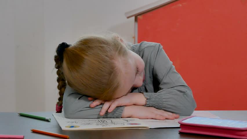 Tired and bored little preschool girl sleep on homework desk. Pretty female pupil do homework and school exercises. Home education concept | Shutterstock HD Video #1024112252