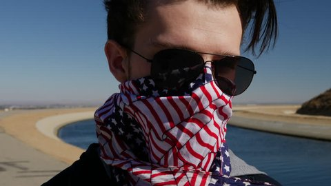 Close up slow motion shot of a handsome young white man in a bandit mask and aviator sunglasses with a red white and blue American flag bandana.