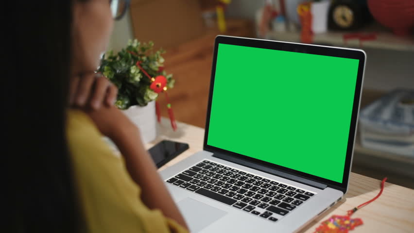 Over the shoulder shot of woman with  laptop computer green screen being on the table among wrapped Chinese New Year presents in the decorated for Chinese New Year at home. Alpha channel. | Shutterstock HD Video #1024124702