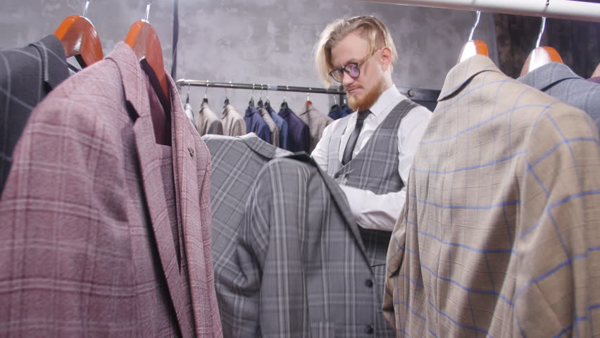 Shopping and fashion concept - Young bearded man choosing and trying jacket on in mall or clothing store | Shutterstock HD Video #1024153322