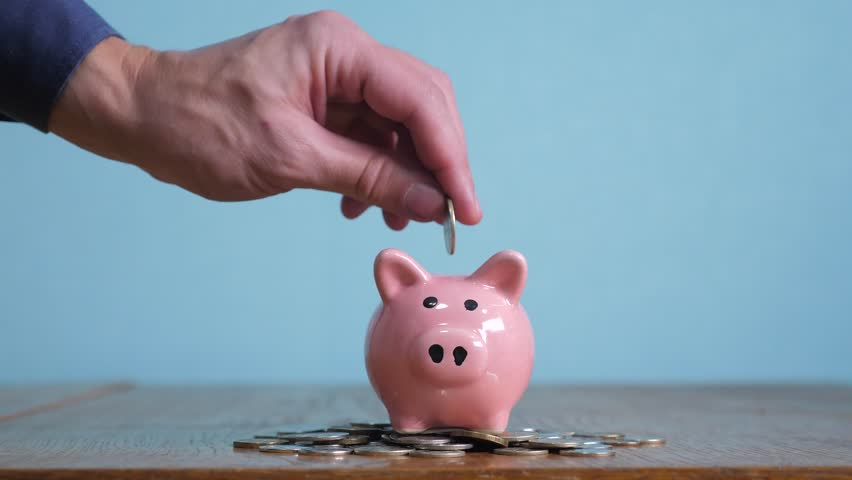 Piggy bank business standing on a pile of coins concept. A hand is putting a coin in a piggy bank on a yellow background. saving money is an investment for the future lifestyle. Banking investment | Shutterstock HD Video #1024169972