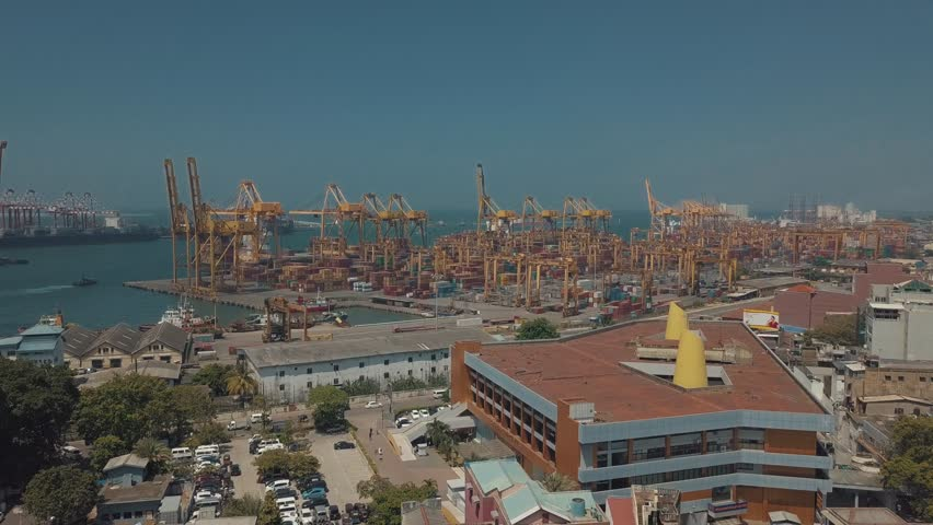 Aerial drone point of interest above the large cargo ship terminal/ container port docklands in the capital city of Colombo in Sri Lanka with large yellow cranes working on a sunny day by the harbor