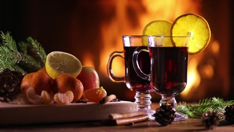 Two glasses of mulled wine (gluhwein) and a plate of fruit on the background of a burning fireplace