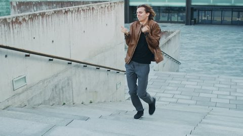 Happy Young Man with Long Hair Actively Dancing While Walking Up the Stairs. He's Wearing a Brown Leather Jacket. Scene Shot in an Urban Concrete Park Next to Business Center.