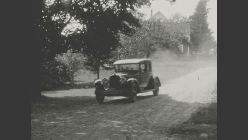 1930s: Large automobile drives up dirt road, arrives at country house.