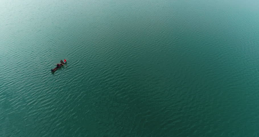 Aerial above view of a small boat on the rippling river, one man rowing the boat carrying few people
