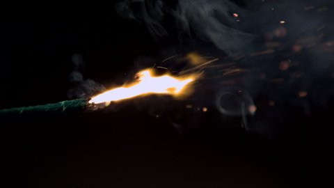 Firework fuse burning in close up slow motion with black background filmed with high speed camera