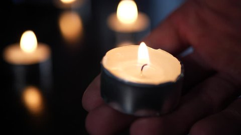 A hand holding a tealight candle on fire in a church temple with other candles burning and heavy background blur bokeh behind.