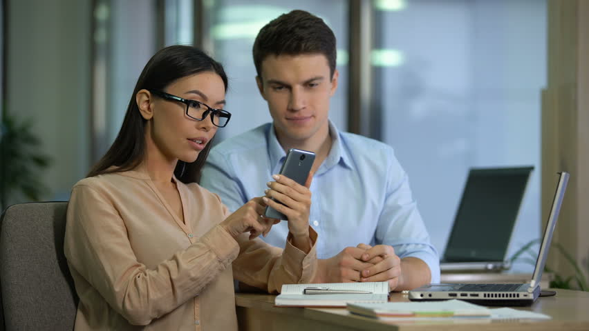 Happy asian caucasian colleagues checking mail on gadget, surprised by good news | Shutterstock HD Video #1024506812