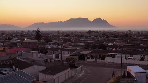GUGULETHU, SOUTH AFRICA - CIRCA 2018 - Spectacular aerial over township in South Africa, vast poverty and ramshackle huts, at night or dusk.