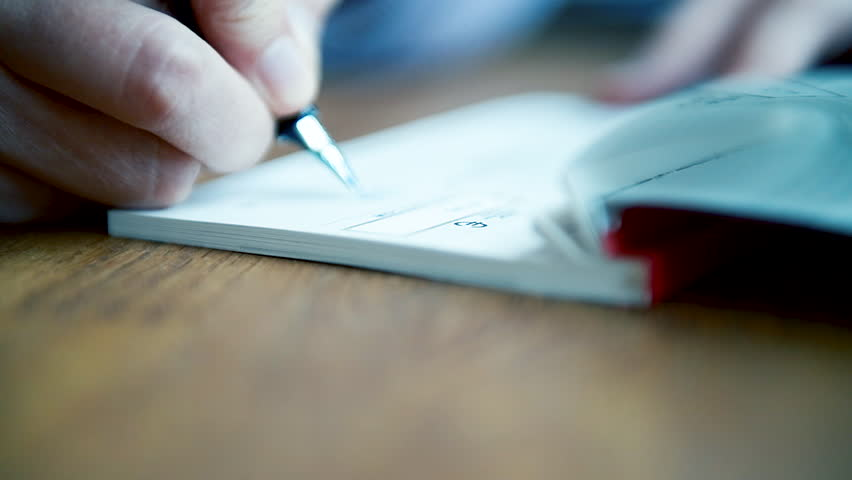 Macro close-up detail of young business woman filling a banking cheque check writingwith luxury fountain pen the requested data in the luxury first class checkbook | Shutterstock HD Video #1024582382