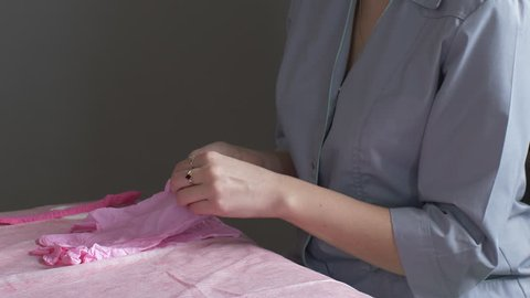 Portrait of beautician doctor in gray medical clothes, with pink gloves and mask on his face. doctor is preparing to perform anti-aging procedures on couch.