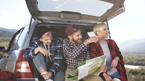 Happy hipster friends are looking at the road map while sitting in front of the travel car trunk with the smile. Friends inside a trunk car planning a road trip of mountains looking at a map, slow