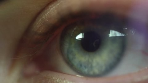 Extreme close up shot of eye of concentrated blue eyed woman looking closely at something