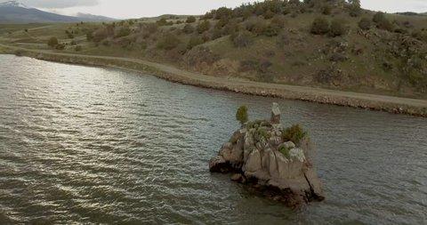 Stunning shallow Ennis Lake rock island at Bear Trap Canyon landscape next to the shores (drone shot)
