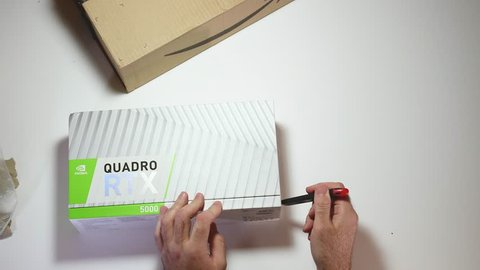 Paris, France - Feb 20, 2019: Man unboxing latest Nvidia Quadro RTX 5000 workstation professional video card GPU for professional CAD CGI - open carefully the package