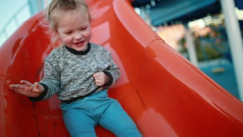 A young toddler laughs and enjoys the playground at a park as he slides down the slide.