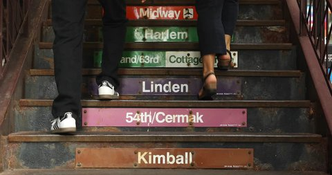 "Chicago, Illinois, USA - September 25, 2018:  People walk up  the stairs to the elevated ""El"" Train station direction signs on the stairway of Wabash Avenue in Chicago Loop"