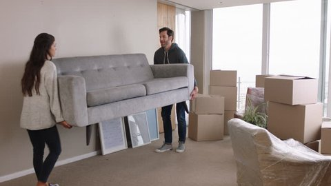 young couple moving house new home owners smiling enjoying successful move hugging in apartment