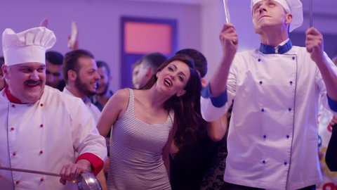Cook dancers having fun dancing at a colorful party . Funny cook chef in white uniform, with a hat and ladle , smiling and partying during party . Shot on RED EPIC Cinema Camera in slow motion .