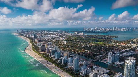MIAMI, FLORIDA, USA - JANUARY 2019: Aerial hyperlapse 4k drone panorama view flight over South Miami and Mid-Beach ocean coastline. Miami Beach Boardwalk from above at sunny day.