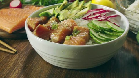 Poke bowl, traditional Hawaiian raw fish salad with rice, avocado, cucumber and radish on wooden background