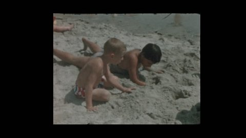 New York, New York, USA- 1956: Happy kids dig in sand at beach and young girl sticks her tongue out
