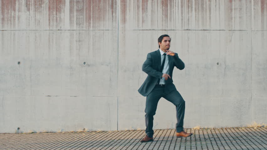 Cheerful and Happy Businessman is Actively Dancing on a Street Next to an Urban Concrete Wall. He's Wearing a Grey Suit. Sunny Day. | Shutterstock HD Video #1024862372