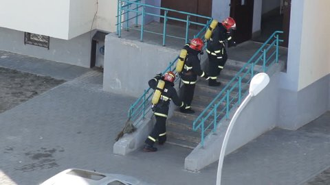 A group of firefighters runs into the house to evacuate people and extinguish the fire, professional