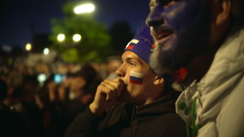 Football fan shouts, rejoices goal favorite 4K team. Person paint face jump in delight victory match. Closeup guy screaming furiously, jumping with friend against backdrop crowd winning football game