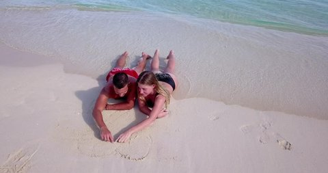 Young couple in love draw heart in sand as shot pulls back and reveals secluded beautiful Maldives sandy beach 4k