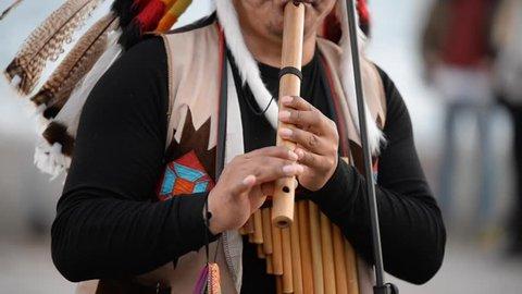 Izmir, Turkey - March 2, 2019: American Indian man playing some wind instruments on the street at Karsiyaka Ferry, Izmir Turkey.