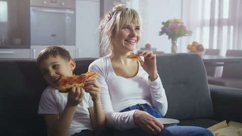 Adorable little boy and beautiful adult mother laughing while watching comedy TV show sitting on couch in domestic interior. Joyful family spending time viewing funny show on TV and eating pizza