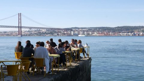 Lisbon, Portugal - March 2nd, 2019: People relax in outdoor restaurant terrace overlooking the iconic 25 April bridge in Lisbon, Portugal - 4K