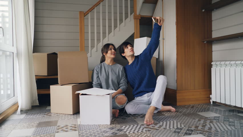 Happy family husband and wife are taking selfie with house keys sitting on floor of new apartment near carton boxes with things. Relocation and social media concept. | Shutterstock HD Video #1025078012