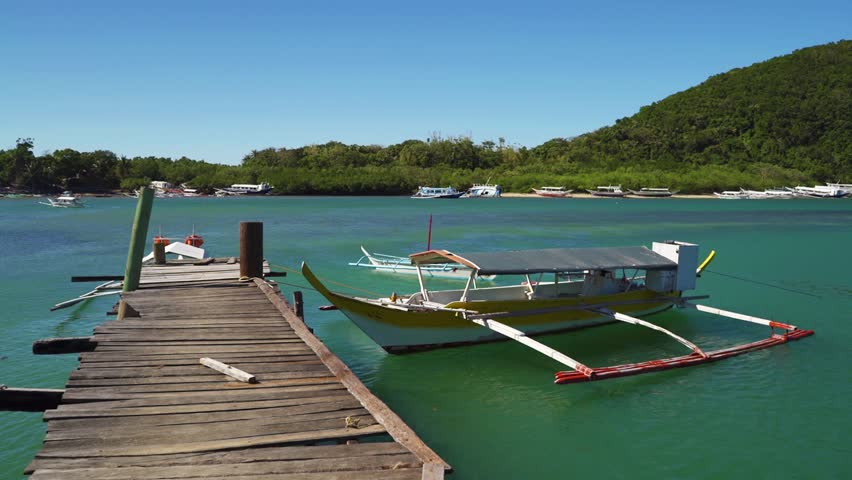 Filipino Bangka Boats Attached to a Wooden Pier in Puerto Gallera, Philippines #1025127482