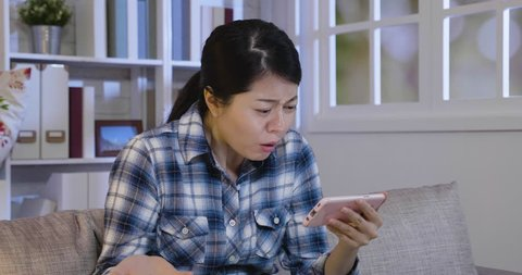 young girl relax watching series online in sofa at home shocked surprised by error of cellphone. asian lady unsatisfied with bad internet connection wifi in house. film stopped on smart phone.