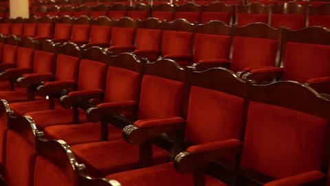 Soft red velor or velvet chairs in the opera house. Rows of empty spectator seats before the start of the performance. Point of view, the first perspective of the viewer, who goes to his place.