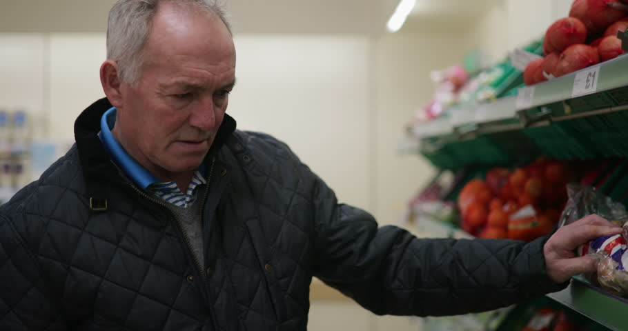 Senior man is buying fruit and vegetables in the supermarket.