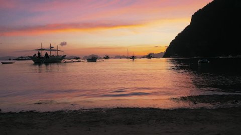 Gimbal steadycam shot of traditional philippine boats bangka at sunset. Beautiful sunset with silhouettes of philippine boats, El Nido, Palawan island, Philippines. Orange sky sunset paradise beach.