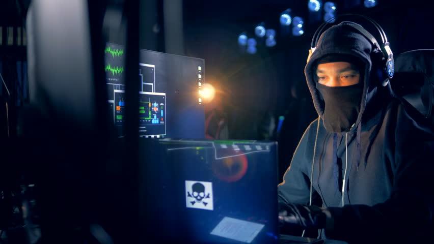 Male hacker in a mask is breaking into the system | Shutterstock HD Video #1025305952