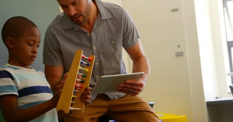 Front view of young Caucasian male teacher teaching schoolboy to use abacus in classroom. Teacher holding digital tablet
