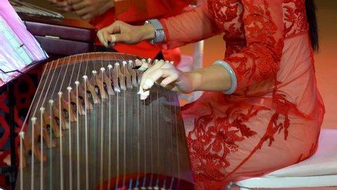Chinese traditional musician playing chinese guzheng,