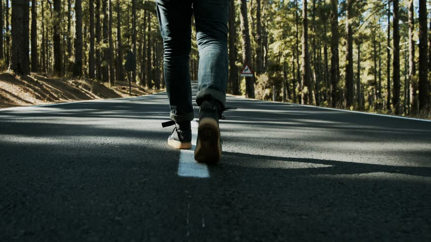Close up follow shot of male sneackers or hiking shoes walk in middle of small mountain road in forest. Concept of walking and reaching goals. Urban nomad adventurer on hitchhiking trip | Shutterstock HD Video #1025339912