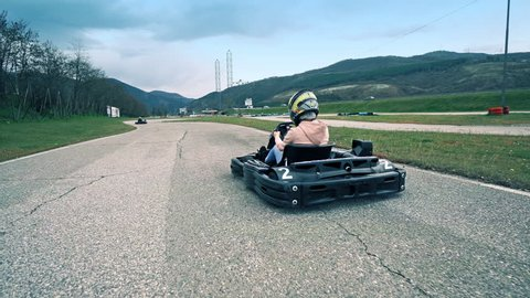 Blagoevgrad, Bulgaria - April 07, 2018: Teen driver drive go kart on outdoor track, cinematic steadicam shot