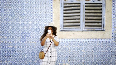 Young lady taking selfie on smartphone at background azulejo painted tin-glazed ceramic tile work on walls in Lisbon